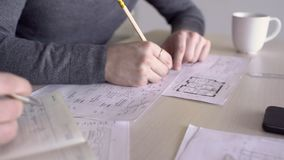 Group of architects at desk works with drawings on notes in the diary. Two men using office supplies prepare project on paper at table for delivery to customer stock video footage