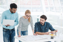 Group of architects discussing plans in modern office Royalty Free Stock Images