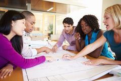 Group Of Architects Discussing Plans In Modern Office. Looking Down Royalty Free Stock Photos