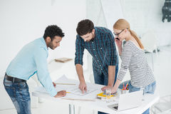 Group of architects discussing plans in modern office Stock Images