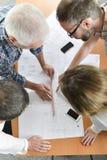 Group architects gathered around desk Royalty Free Stock Image