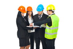 Group of architects having conversation. Group of four architects with hard hats  having conversation and holding blueprints isolated on white background Royalty Free Stock Image