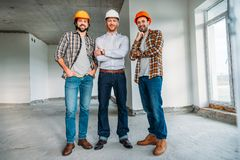 Group of architects inside of constructing building looking. At camera royalty free stock photo