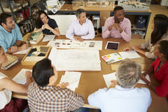 Group Of Architects Sitting Around Table Having Me Stock Image