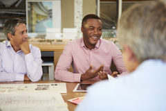 Group Of Architects Sitting Around Table Having Meeting Stock Photos