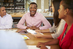 Group Of Architects Sitting Around Table Having Meeting Stock Image
