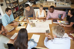 Group Of Architects Sitting Around Table Having Meeting Stock Photo