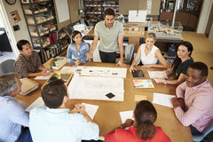 Group Of Architects Sitting Around Table Having Meeting Stock Images
