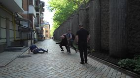 Group of armed muggers attacking male on city lane. Gang of criminals stopping man walking on street in loneliness. Skillful young male fighting with muggers stock footage
