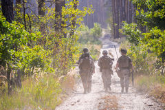 Group of armed soldiers on the road in forest. Group of soldiers incamouflage on the road in forest royalty free stock image