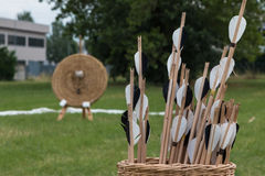 Group of Arrows inside Wicker Basket and Straw Archery Target in Royalty Free Stock Photography