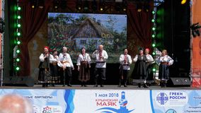 A group of artists in folk costumes on the open stage performs and sings songs. YALTA, RUSSIA, MAY 1, 2018: A group of artists in folk costumes on the open stage stock video