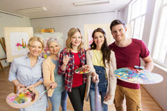 Group of artists painting at art school studio. Creativity, education and people concept - group of artists or students with brushes and palettes painting on stock photography