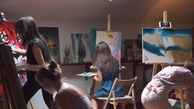 A group of artists paints on canvas in workshop stock video footage