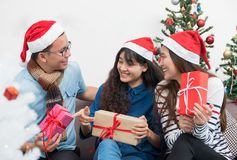 Group of asia friends sitting on sofa celebrate christmas and ne. W year party with gift exchange at decorate tree,gift giving holiday concept.happiness moment royalty free stock photos
