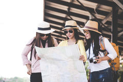 Group of asia women traveler and tourist traveling backpack holding map and waiting in a train station platform, vintage tone. Travel Concept stock photos