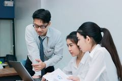 Group of Asian business people working together in modern office. Selective focus and shallow depth of field. Group of Asian business people working together in Stock Images