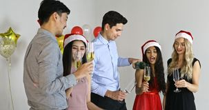 Asian and Caucasian sharing alcohol together. Group of Asian and Caucasian people in New year party, holding glasses and sharing some alcohol and give a toast
