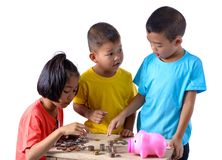 Group of asian children are helping putting coins into piggy ban stock photography