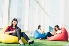 Group of Asian college student or business colleague using smartphone sit together in modern office or university campus stock photo