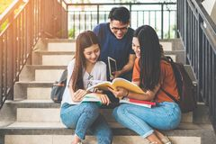 Group of Asian college student using tablet and mobile phone outside classroom. Happiness and Education learning concept. Back to royalty free stock images