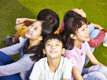 Group of asian elementary schoolchildren. Group of asian elementary school boys and girls sitting on playground grass looking up at the sky Stock Photos