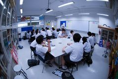 Group of Asian Elementary students are learning about electricity in classroom. royalty free stock images