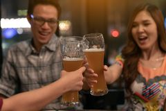 Group of asian friends holding pint glass of beer toasting for drink on Friday night in relaxing after work TGIF concept. Attractive young asian couple join stock image