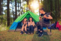 A group of Asian friends tourist drinking and playing guitar together with happiness in Summer while having camping.  royalty free stock image