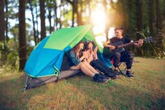 A group of Asian friends tourist drinking and playing guitar together with happiness in Summer while having camping.  stock image
