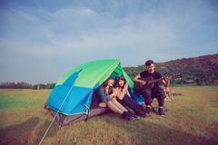 A group of Asian friends tourist drinking and playing guitar together with happiness in Summer while having camping near lake at. Sunset royalty free stock image