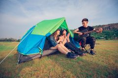 A group of Asian friends tourist drinking and playing guitar together with happiness in Summer while having camping near lake at. Sunset stock photography
