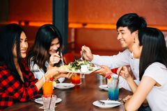 Group of Asian happy and smiling young man and women having a meal together with enjoyment and happiness. royalty free stock images