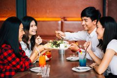 Group of Asian happy and smiling young man and women having a meal together with enjoyment and happiness. stock images