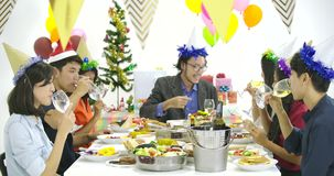 Group of asian people toasting at table together and celebrating Christmas with delicious meal at new year party. People with holidays and celebration concept