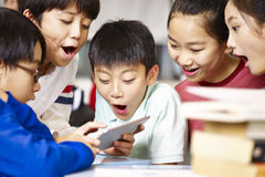 Group of asian primary school pupil playing game using tablet Royalty Free Stock Photo