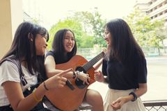 Group of asian teenager standing outdoor plying spanish guitar and dancing with happiness emotion stock images