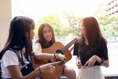 Group of asian teenager standing outdoor plying spanish guitar and dancing with happiness emotion royalty free stock image
