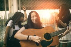 Group of asian teenager standing outdoor plying spanish guitar and dancing with happiness emotion. Group of asian teenager  standing outdoor plying spanish stock photo
