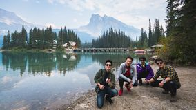 Group of Asian tourist sitting on the beach at the Emerald Lake is located in Yoho National Park, British Columbia, Canada stock image