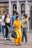 Group of Asian tourists on a sunny Dam Square, Amsterda,