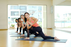 Group of asian women training yoga indoor class in namaste posture with joyful, relax and meditate emotion. Wellness, well being and healthy lifestyle concept royalty free stock image