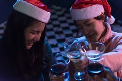 Group Asian young friends Enjoying Evening Drinks together party. With Disco lights celebrating Christmas at dark home, Christmas or New Year concept Stock Photos