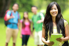 Group of asian youngers backpacking, focused on female backpacke. A portrait of beautiful asian women backpacker and holding a map, friends at the background Royalty Free Stock Photos
