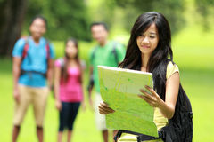 Group of asian youngers backpacking. A portrait of beautiful asian women backpacker and holding a map, friends at the background Royalty Free Stock Image