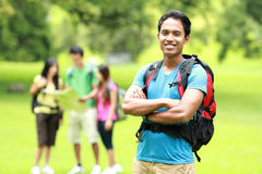 Group of asian youngers backpacking. A portrait of handsome men backpacker and a group of asian youngers backpacking at the background royalty free stock photography