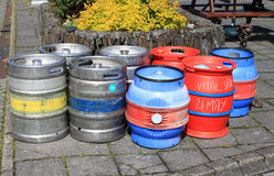 Group of assorted beer barrels on a pavement. Eight beer barrels, some metal and others plastic, stand on a pavement either after a delivery or awaiting Royalty Free Stock Images