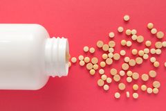 Group of assorted beige tablets. Capsules spilling out of white Royalty Free Stock Photo