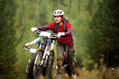 Group of athlete mountainbikers climb a step uphill in forest Stock Images