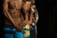 group athletes bodybuilders in colorful summer shorts at competitions in beach bodybuilding royalty free stock photography